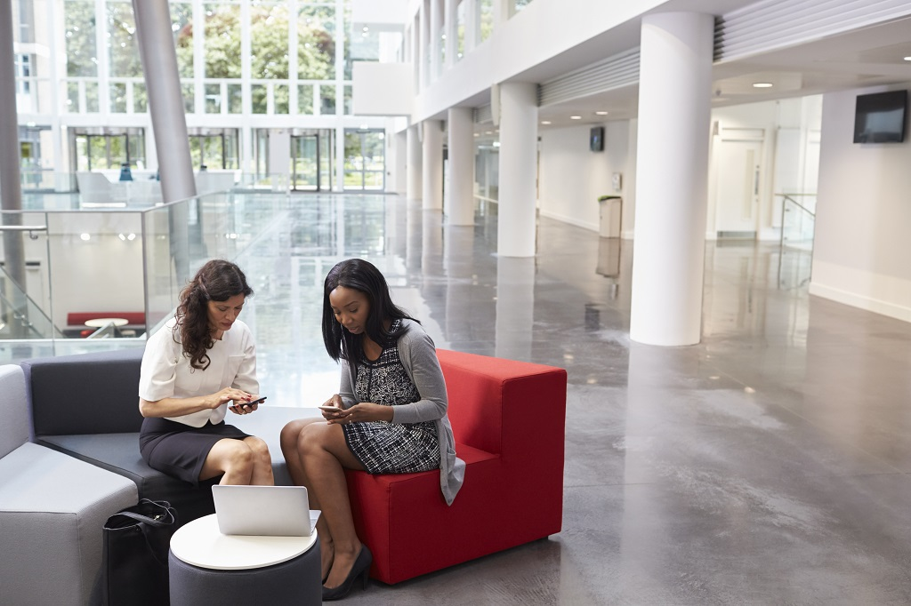 Two Businesswomen Using Mobile Phones In Lobby Of Office; Shutterstock ID 479711017; Departmental Cost Code : 162800; Project Code: g; PO Number: g