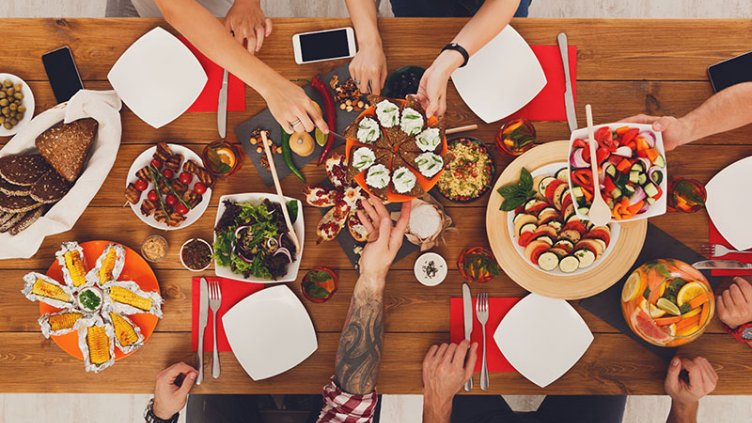 People eat healthy meals at festive table served for party. Friends celebrate with organic food on wooden table top view. Happy company having lunch, taking sandwiches from dish