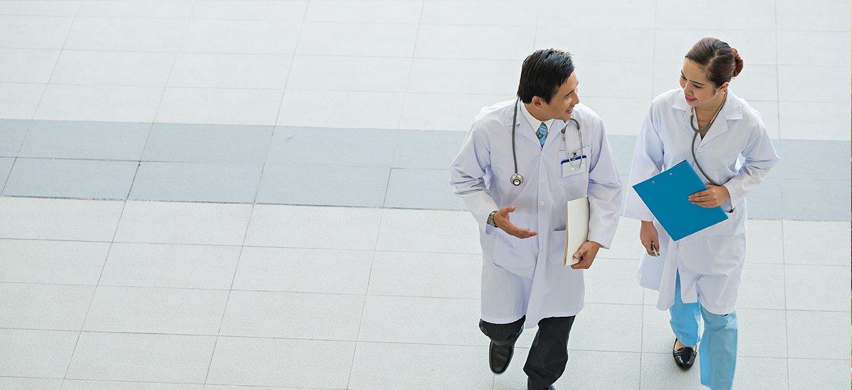 male and female doctors walking down hospital hall